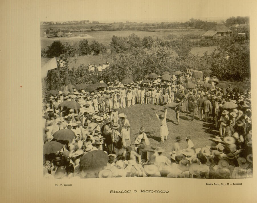 """SINULOG AS WAR DANCE. This photograph is of a sinulog or moro-moro performed in Jaro, Iloilo. It appears """"Recuerdos de Filipinas"""" by Felix Lauereano that was published in 1895. Sinulog is mentioned as a fiesta dance in Panay island with roots in Jolo."""